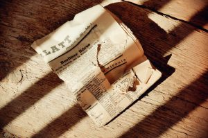 Torn, Old Newspaper On a Wooden Floor