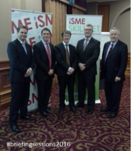 Five Men in font of Isme Signs Smiling